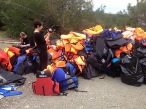 French Journalist filming the pile of life jackets collected by volunteers on Lesvos
