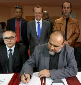 United Nations Special Representative and Head of the U.N. Support Mission in Libya Martin Kobler looks on as representatives of Libyan municipalities sign documents to support Libya's new national government.